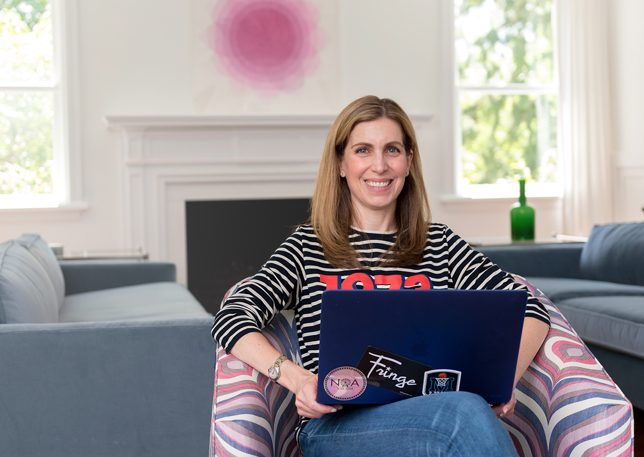 A photo of Jessica Zirkel-Rubin, a smiling woman with medium blond straight hair and pale skin, seated in front of a fireplace with a laptop on her lap.
