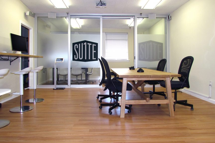 Suite1 Office in Millburn, NJ | An indoor view of an office with a long, wall-mounted desk and bar stools, a lower large table with office chairs, and a glass-walled conference room with a large Suite 1 Logo on the door.