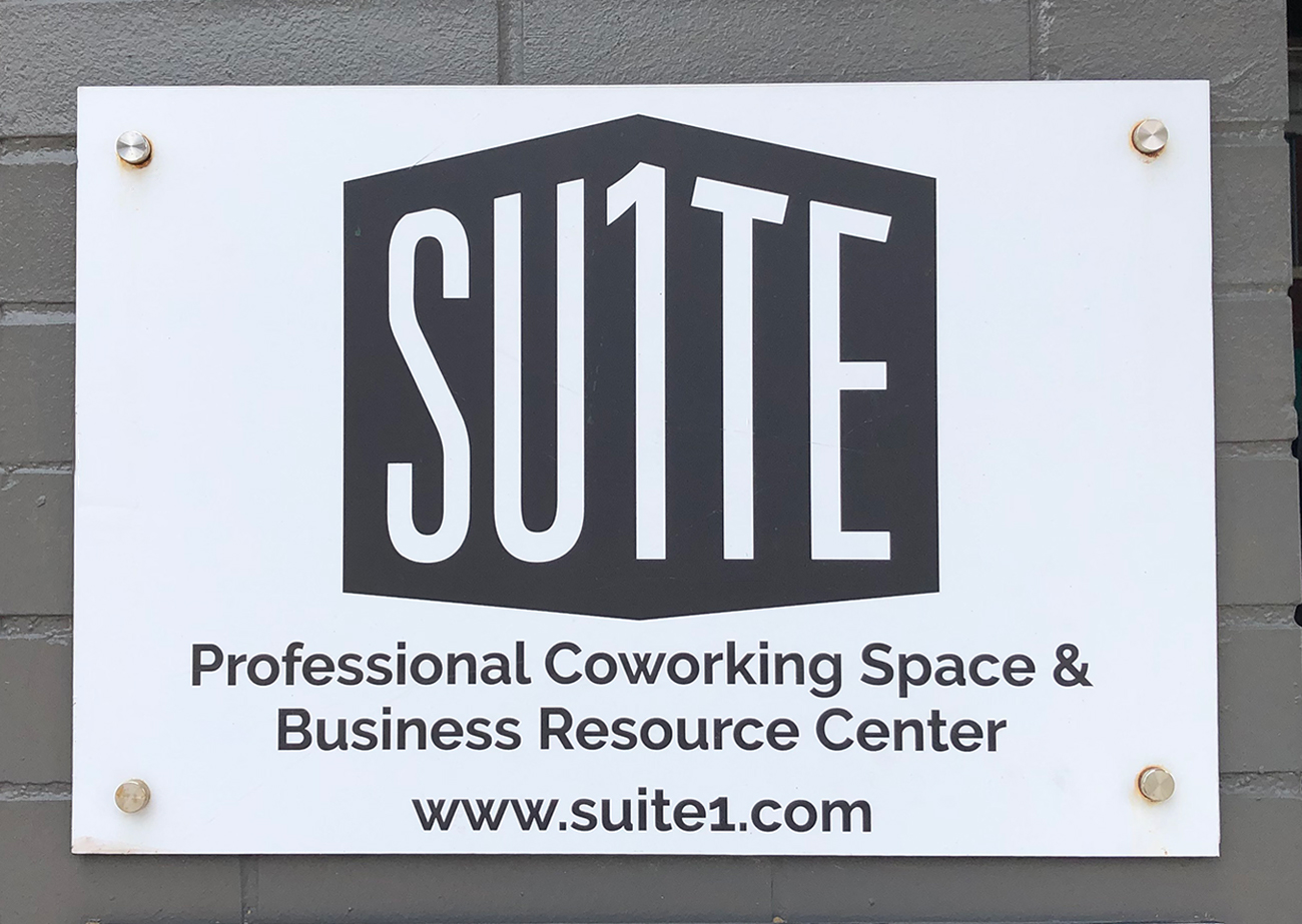 A white sign mounted with silver pegs against a gray-painted brick wall. On the sign is Suite 1 Logo | A black polygon on white ground with white letters that say SU1TE in a sans-serif font.