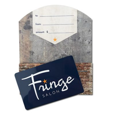 Fringe Salon Gift Card | Gift card is navy blue plastic with white logo. Gift card enclosure has semi-circular flap printed with brick and aged metal patterns. Flap has fields to write to, from, and gift amount.