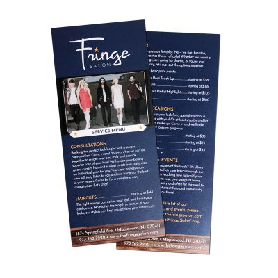 Fringe Salon service menu | Front of salon service menu has white logo and text on navy background, plus picture of male and female models standing in a row. Back has list of services and pricing. Both sides have weathered wood texture on the bottom, overlaid with contact info in white sans-serif text.