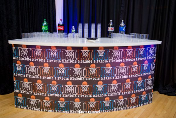 Curved bar with bar mitzvah logo in repeat pattern on front, sodas and plastic cups on bar top.
