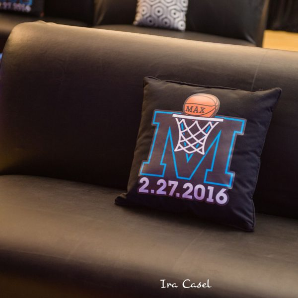 Black pillow with basketball bar mitzvah logo on black couch.