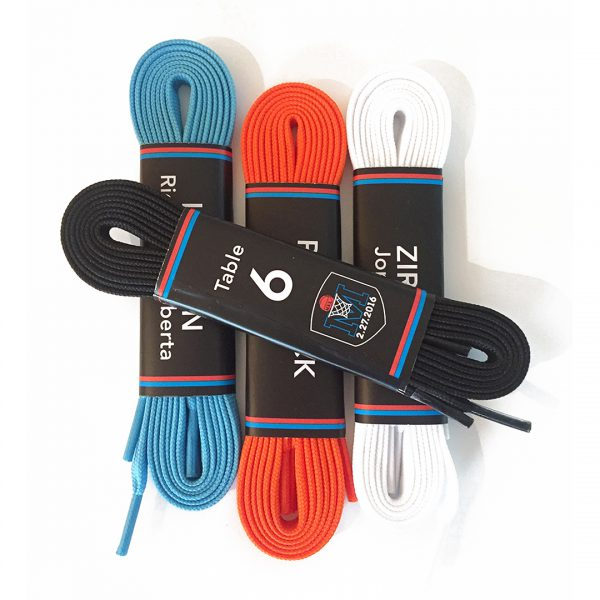 Rolled blue, orange, white and black shoelaces, wrapped with names and table numbers.