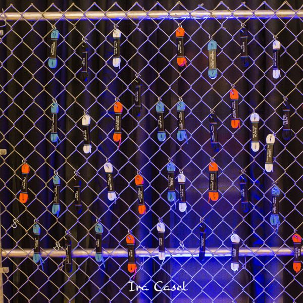 Bundles of white, blue, orange, and black shoelaces, wrapped with guests' names and table numbers, hanging from a chain-link fence.