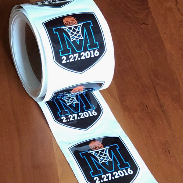 M basketball logo sticker, shaped like a 3 inch shield, repeating vertically on a roll of stickers.