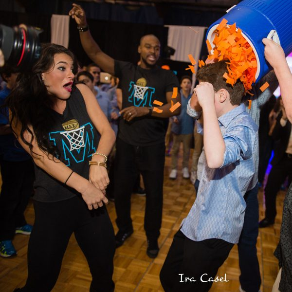 Female and male dancer wearing M basketball logo t-shirts, reacting to boy getting orange paper dumped on his head.
