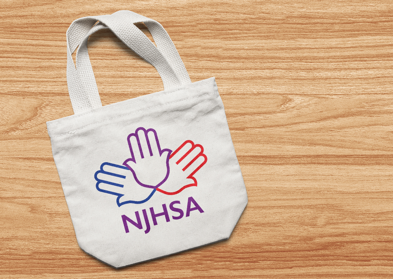 NJHSA Logo Bag | Logo is 3 Hamsa symbols arranged in a fan joined at the base of the palm. Colors are blue, purple and red with the letters NJHSA in purple capital sans-serif letters beneath. Logo is superimposed on off-white canvas tote bag.