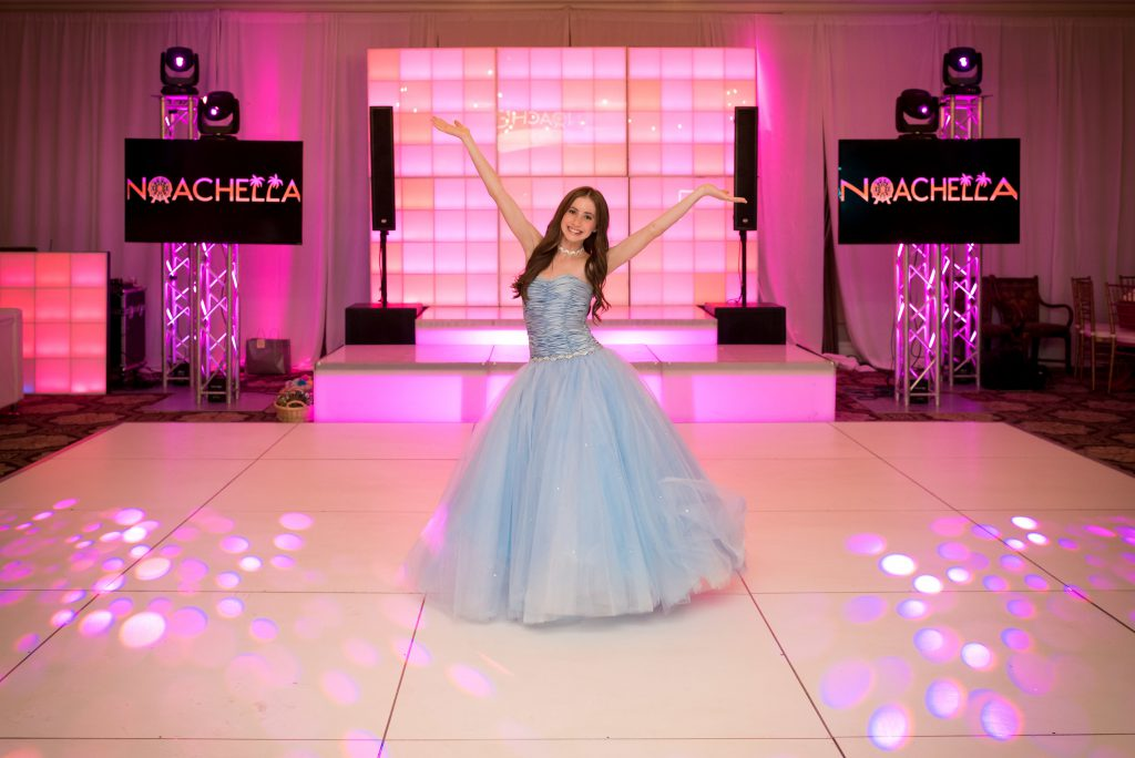 Elated girl in blue ball gown on white dancefloor in front of lighted backdrop that is shades of pink and orange. Noachella and Noa logos shown on TV screens flanking the girl.