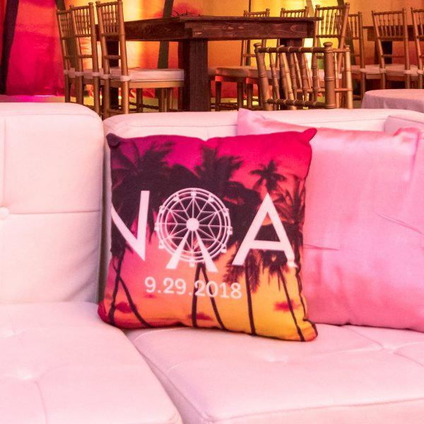 White lounge sofa with square throw pillow with logo and palm tree photo printed on it.