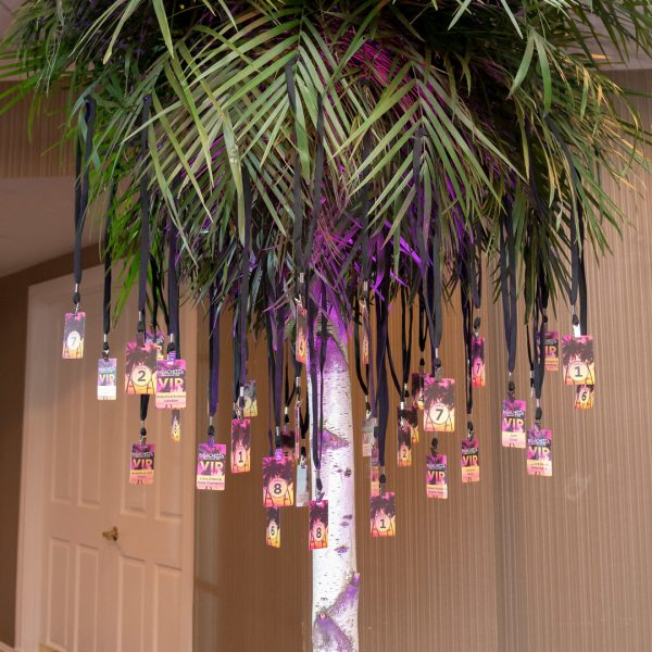 Life-size palm tree with VIP table numbers hung from branches.