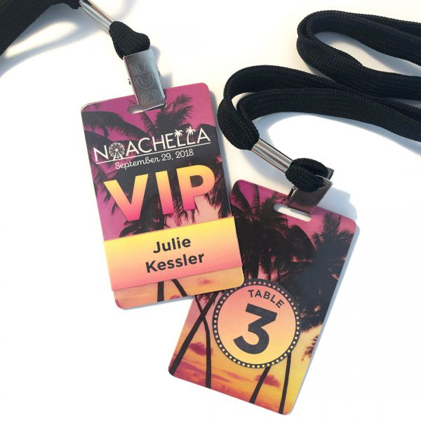 Plastic VIP pass cards, printed with logo and palm tree photo, guest's name on one side and table number on the other, hung from black lanyard with silver metal clip.