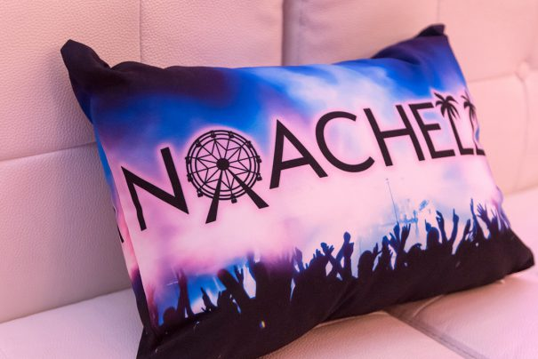 Custom rectangular pillow with Noachella logo printed on photo of a concert stage; mostly blue and black tones.