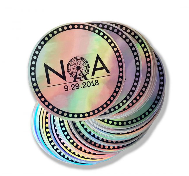 Stack of circular, holographic logo stickers with Noa logo imprinted in black.