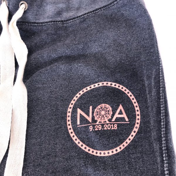 Detail of left upper hip on grey sweatpants with peach/pink printed logo.