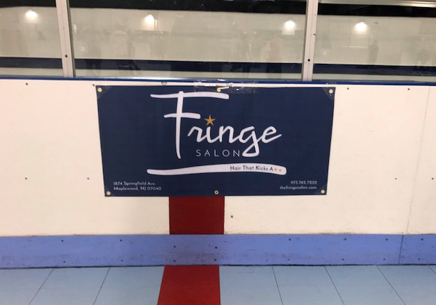 Fringe Banner | Navy vinyl banner with white and orange logo, hung on wall in roller rink.