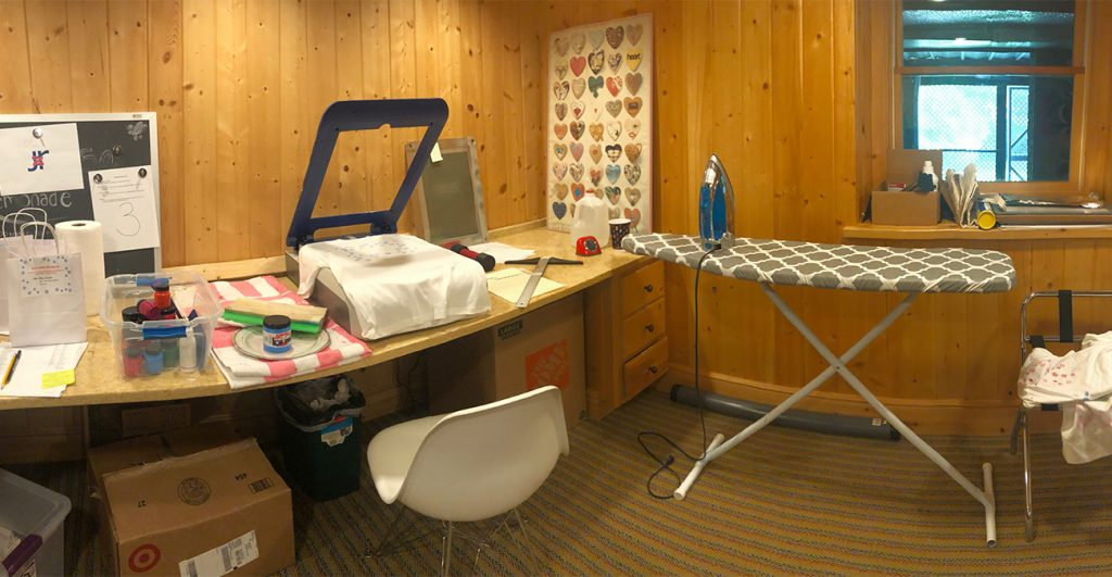 Photograph of wood-paneled basement with bin of screenprinting ink, squeegee, Yudu machine, timer, screen, and T-square on desk. Ironing board is nearby.