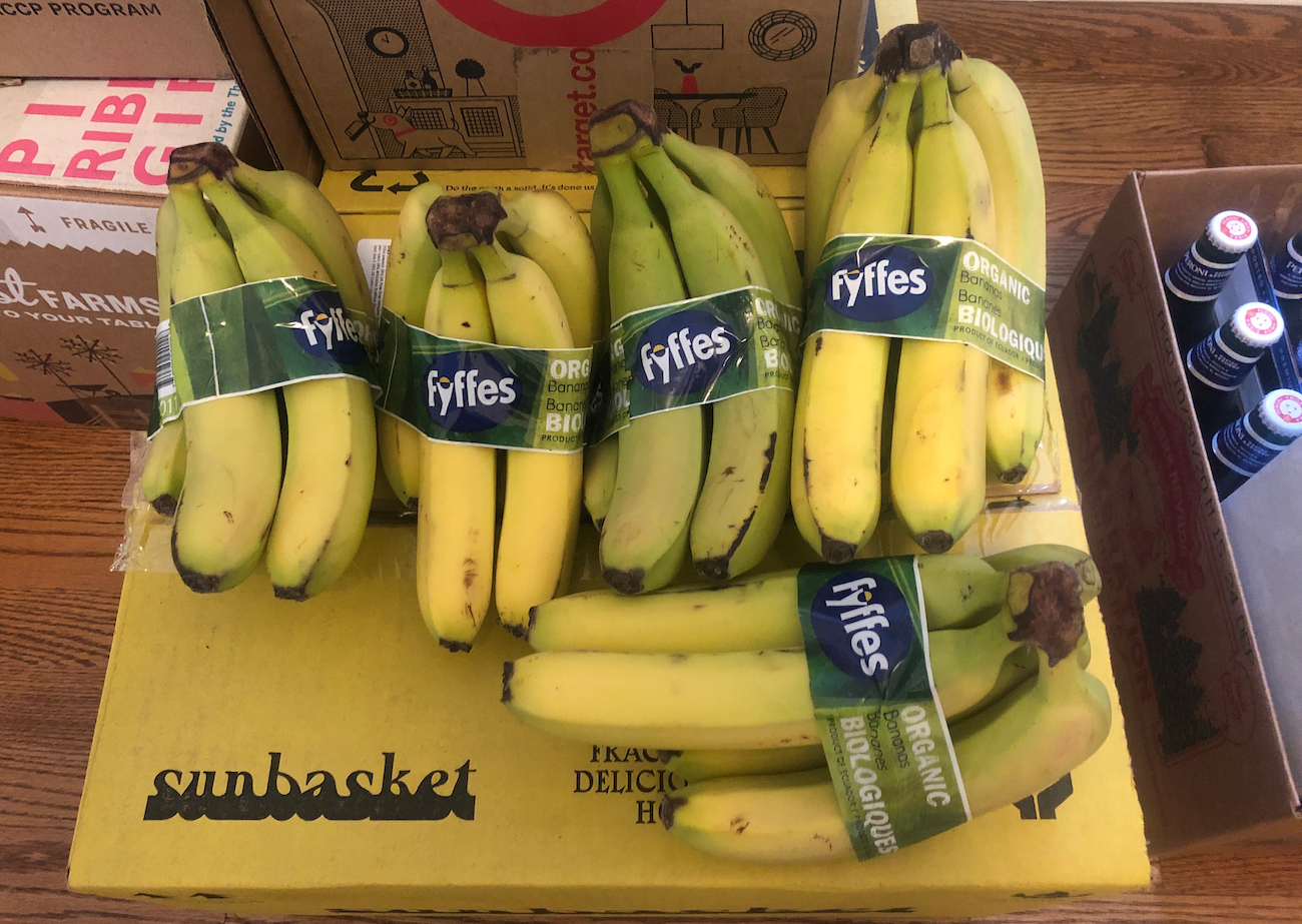 Photo of 5 bunches of bananas stacked on a shipping box.